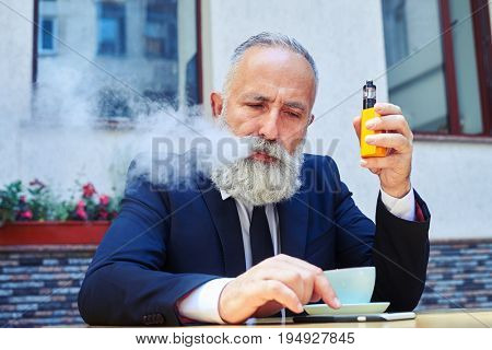 Mid shot of man exhaling fume while surfing in phone over cup of coffee