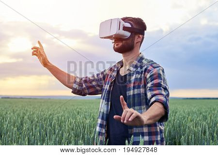 Side view of Guy using 3D glasses. Enjoying time exploring another reality. Standing on field, mid shot
