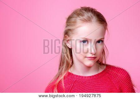 Cute girl teenager over pink background. Studio shot. Teen's fashion.