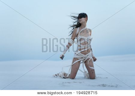 Girl in desert in image of Egyptian mummy with knife in her hand. She kneels all wrapped in bandages and she has hieroglyphics on her body.