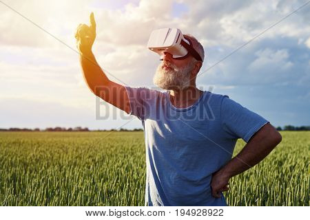 Side view of bearded male alone wearing 3D glasses in plain air on field. Looking up, holding hand on hip, another one pointing