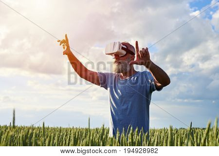 Side view of elderly bearded man using 3D glasses, virtual reality. Male on field pointing on something, mid shot