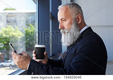 Mid shot of grey sir age of 50-60 holding cup of coffee and surfing in phone while leaning on handrail