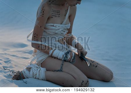 Girl in image of Egyptian mummy sits on sand with metal chain and knife in her hands. She is wrapped in bandages and she has hieroglyphics on her body.