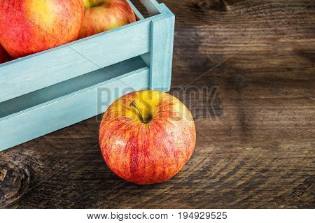 A closeup of a vibrant red and yellow apple in front of a teal crate, on a rustic wooden texture, with copy space, selective focus