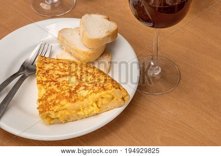 A photo of a tortilla, traditional Spanish potato omelette, with two forks, white bread, glasses of red wine, and a place for text. Typical tapas