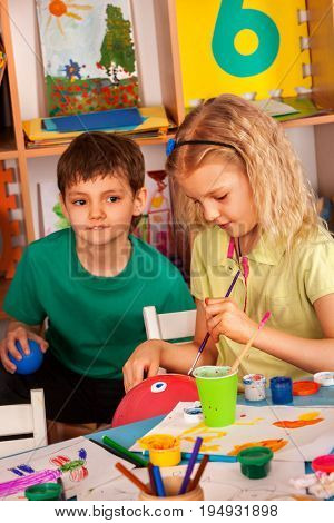 Small students girl and boy painting in art school class. Child drawing by paints on table. Male kid shows his drawing in kindergarten. Boy really likes girl. Child love.
