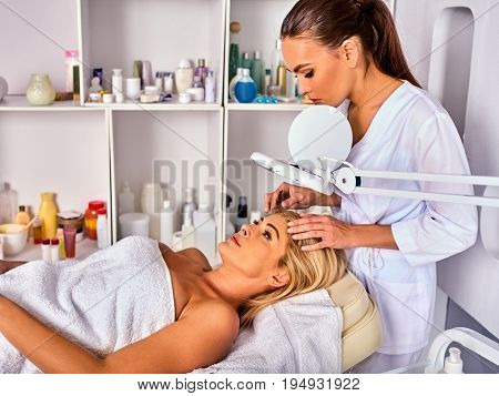 Eyebrow treatment of woman middle-aged in spa salon. Tweezing eyebrow by beautician. 40s old female under cosmetic lamp. European facial procedure. Patient looking up. Medical professional room