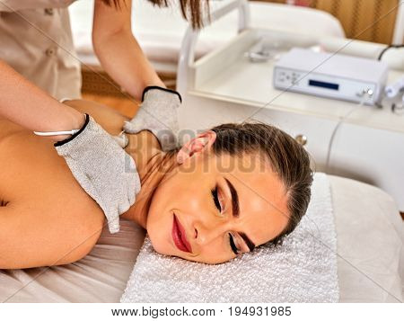 Body massage of silver threaded gloves at beauty salon. Electric stimulation skin care of man. Professional equipment for microcurrent lift . Close up of room is device for hardware cosmetology. poster