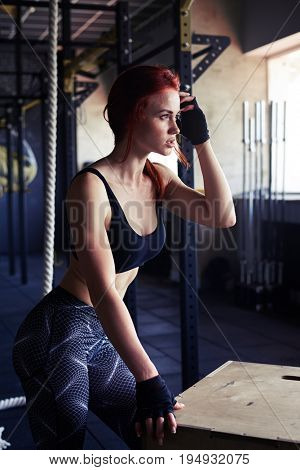 Side view of female taking a break from endurance workout in gym