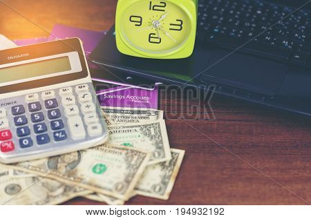 Finance concept : US dollars saving account passbook calculator clock and laptop on wood background