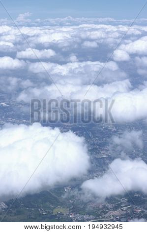 View of white clouds and horizon land below.