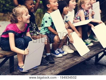 Children are sitting together holding placard