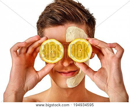 Facial mask from fresh fruits and clay for man concept. Face with treatment mud applied . Male holding lemon half for skin care procedure in salon. Lemon are main ingredient in cosmetic masks