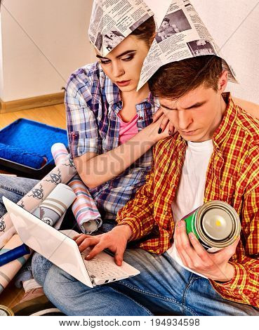 Repair family by happy couple building home using pc. Woman and man in newspaper cap with laptop renovation apartment. People orders goods over internet.