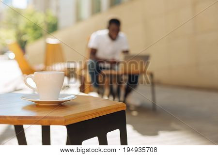Drink for energy. Young handsome ambitious man sitting on a terrace while typing something on his laptop and having a productive day