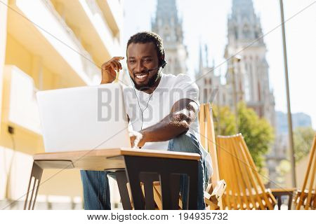No limits. Attractive optimistic easy going man sitting on a terrace and talking to his friend from another county using his computer