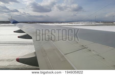 Aeroplane wing taken from airplane window, while airplane moving on ground at an airport, with background of mountain, blue sky, and snow coverring in whole area