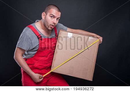 Mover Guy Holding Box Measuring With Tape Looking Surprised