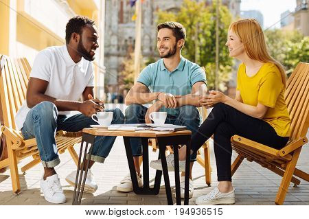 Many topics. Charismatic nice lively man telling how his week going and sharing some interesting stories while meeting with his friends in a cafe