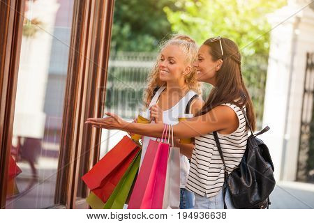 Two happy women are shopping in the city. They are looking at storefront.