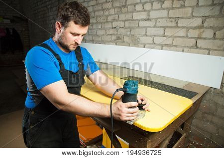 Professional carpenter processes the plastic edges of the countertop with a special electric tool