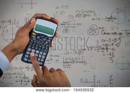 Hands of businessman using calculator  against mathematical problems with diagrams and solution