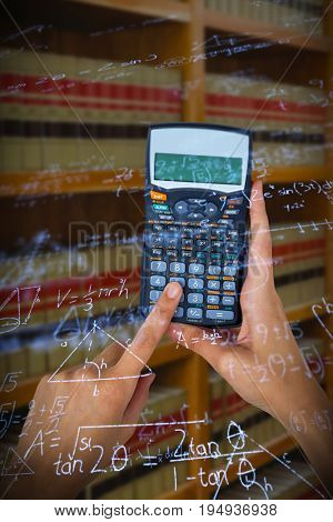 Hands of businesswoman using calculator against digitally composite image of mathematical equations with solution