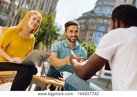 Another point of view. Innovative enthusiastic open minded man meeting his friends in a cafe and giving them the new concept he working while developing their common project