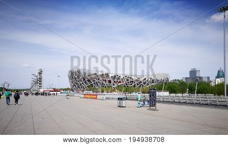 BEIJING, CHINA - APRIL 15, 2017: Beijing National Stadium or Bird's Nest Stadium. Tourists were visiting here. A woman in light-blue-uniform, with cleaning tools, was waiting to do her task.