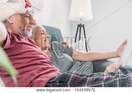 Happy Senior Couple With Digital Tablet Resting In Bed Together
