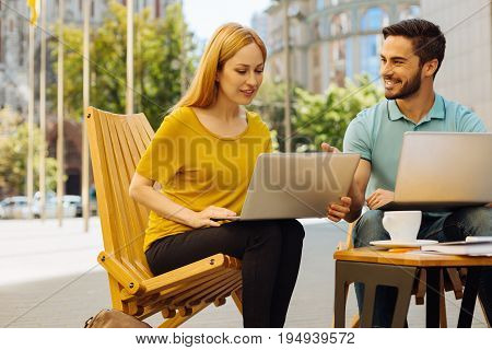 Offering assistance. Lively passionate helpful guy explaining his friend some details of the concept and helping her out with business plan