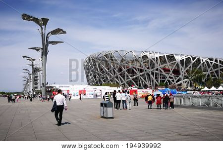BEIJING, CHINA - APRIL 15, 2017: Beijing National Stadium (BNS) or Bird's Nest Stadium. Tourists were taking photos, carrying umbrellas, visiting and walking to look around during day time.