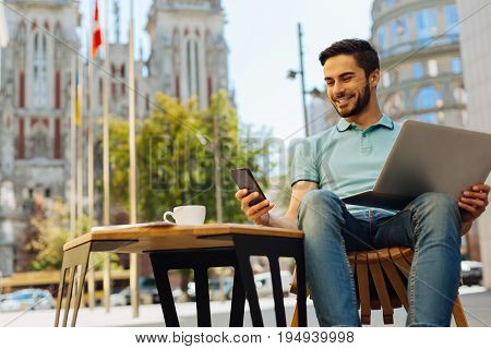Funny reply. Committed analytical talented man taking a moment for checking his email while sitting on a terrace and working on some assignments