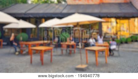 Blurred yellow umbrellas, brown wooden tables and chairs at outdoor cafe or patio; with people activities (sitting, standing, relaxing). For background usage.