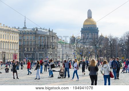 SAINT PETERSBURG RUSSIA - MAY 1 2017: Unidentified tourists are strolling on Palace Square St. Petersburg Russia. Famous St. Isaac's Cathedral is on background