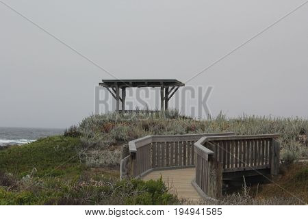 Gazebo and footbridge surrounded by native plants at Asilomar State Beach in Pacific Grove, California on a cloudy day