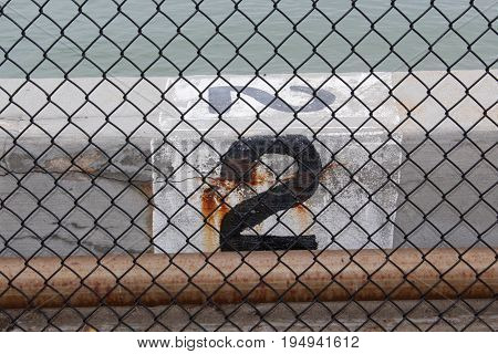 Looking through a black chain link fence at the number 2 painted in black against a white background on a conrete wall