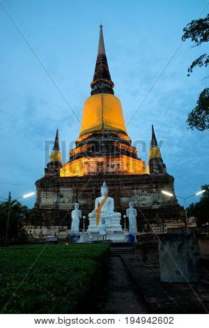 AYUTTHAYA,THAILAND-JULY 9,2017 : Twilight time of white Buddha statues and ruined at Principal Chedi in Wat Yai Chai Mongkhon the Great Monastery of Auspicious Victory is located Ayutthaya Historical Park in Ayutthaya old capital city in Middle of Thailan