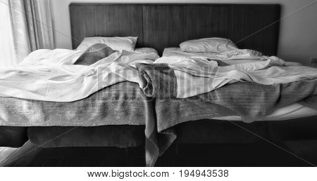 Two adjacent beds in black and white with different light strength. The left one is bright, the right side is dim. Concepts of differentiation, discrimination, conflict, distinction