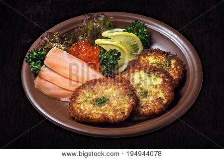 Hash browns with a salmon and caviar isolated on a dark wooden background