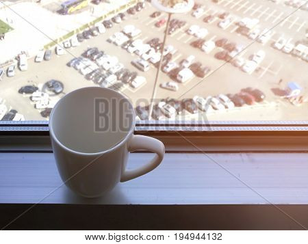 White coffee cup on aluminum window sill; in a room at high level floor of a tall building with car parks view in background. Concept of someone is watching car parking.