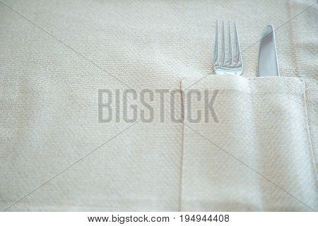 Fork and knife in  napkin. Top view.