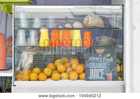Orange juice and fruit shop, Showcase full of oranges and plastic cups