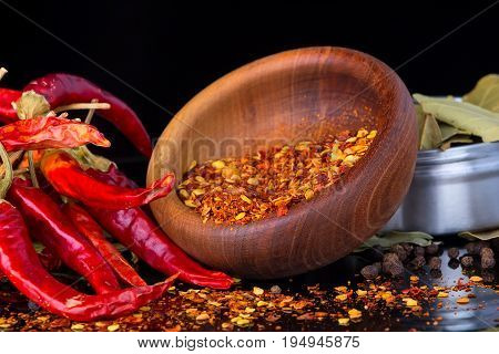 Red chili peppers and chili flakes on a black background with reflection