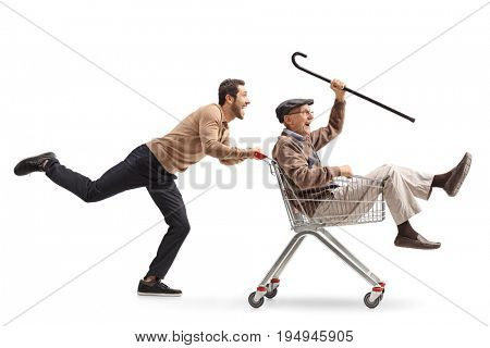 Young guy pushing a shopping cart with a senior inside isolated on white background