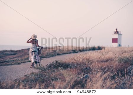 Stylish girl with bicycle walking on road with lighthouse at backgrounds. 20s. Summer season.