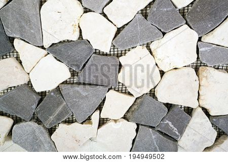 Tile from dolomite stones on a grid on a white background