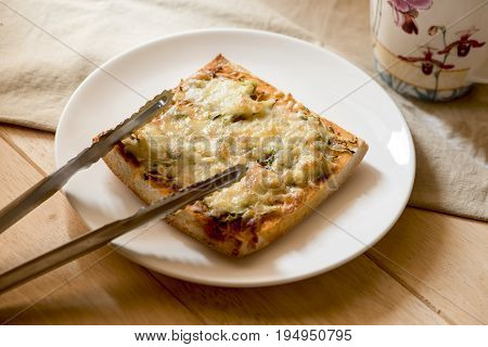 Pizza toast with cheese and steel tongs on the white plate.
