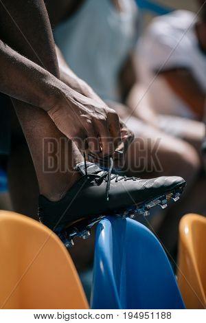 Cropped Shot Of Man Tying Shoelaces While Sitting On Stadium